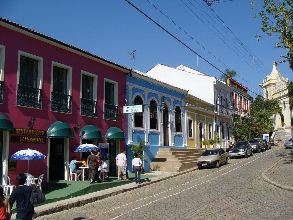 A imagem é de uma rua de antonina, com casas e comércios com paredes coloridas, alguns carros estacionados ao lado e uma igreja antiga ao fundo.