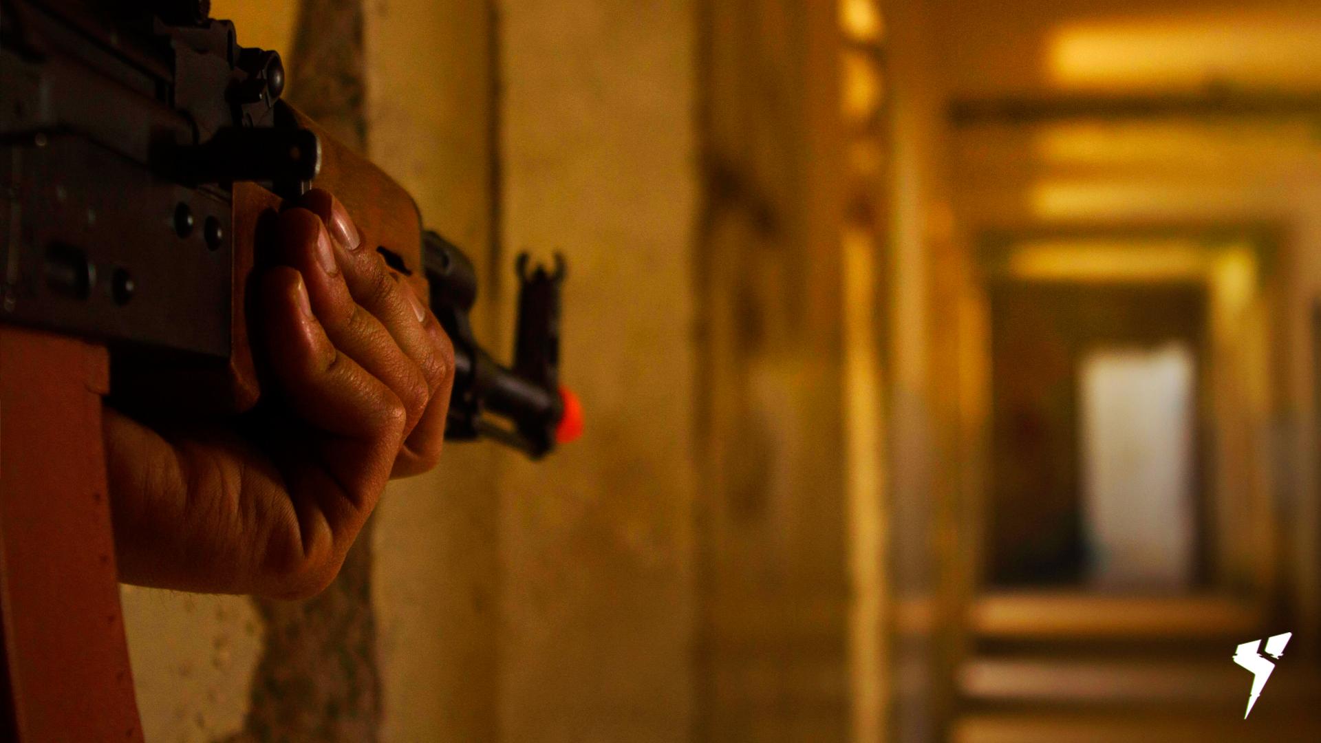 No canto esquerdo uma pessoa está segurando uma AK-47, mirando para o fundo de um corredor. Na imagem aparece apenas uma mão e a arma.