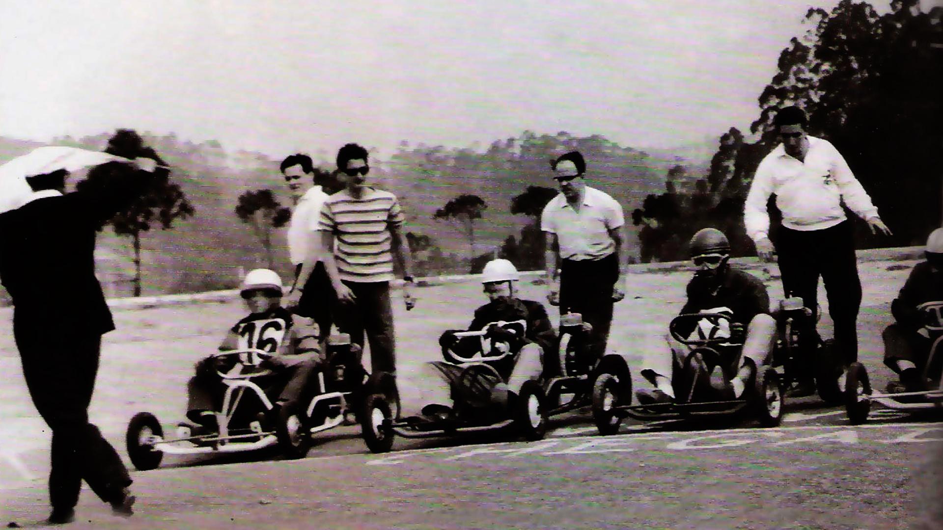 Imagem histórica de uma corrida de kart bem antiga. Na imagem tem 4 pilotos, além de 5 pessoas próximas aos karts.
