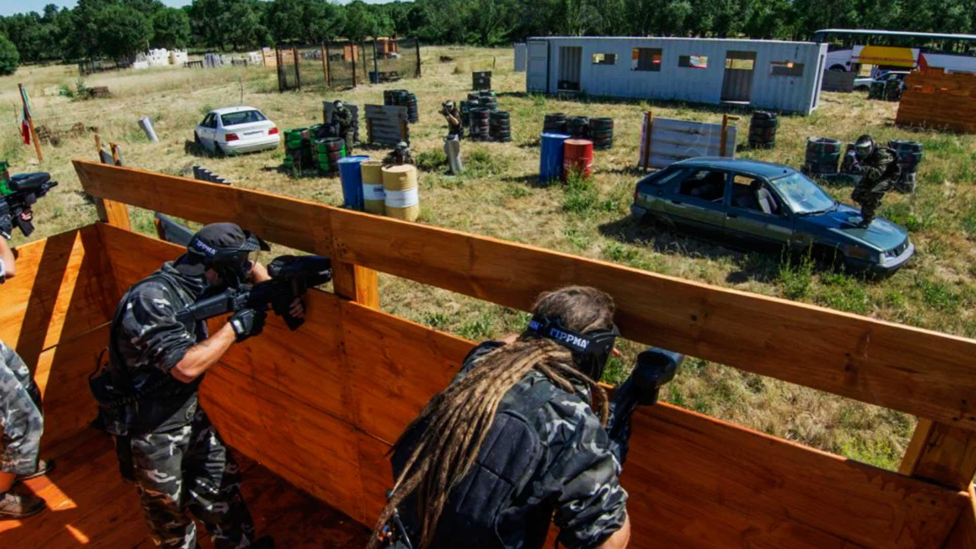 Campo de paintball outdoor, onde duas pessoas estão dentro de uma estrutura de madeira e mirando em dois adversários que estão fora. Um dos que estão fora, está em cima de um carro, já o outro está exporte, ao lado de barris.
