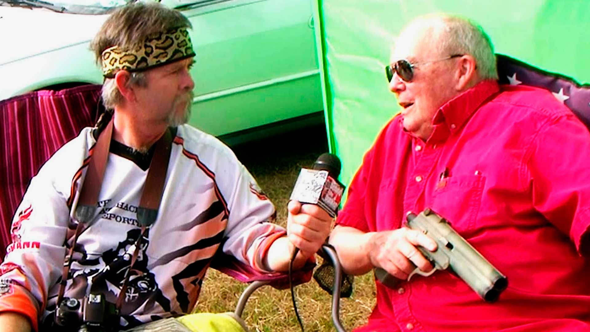 Imagem do Bob Gurnsey, criador do paintball, dando entrevista. Em sua mão ele segura uma pistola.