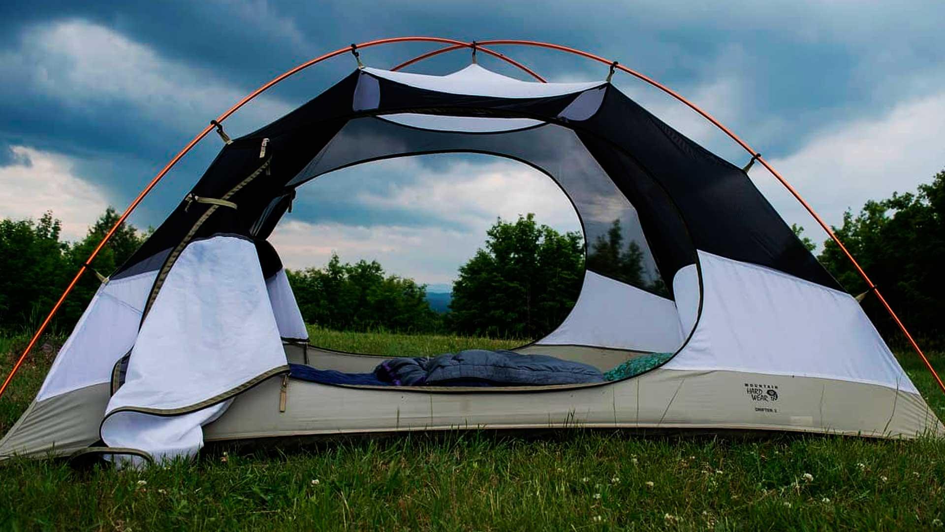 Barraca de camping montada na grama, perto de diversas árvores e com um céu bem azul e com bastante nuvens.