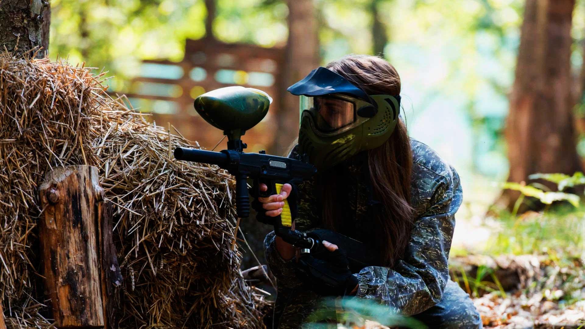 Jogadora de paintball agachada atrás de um entulho de madeiras, mirando para frente.