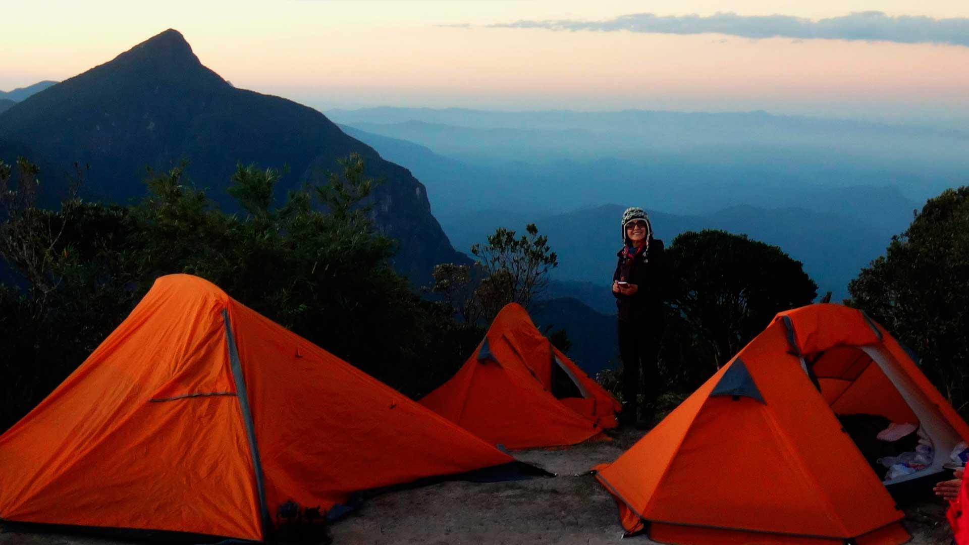 Mulher acampando no pico de uma montanha, com 3 barracas laranjas montadas. Ao fundo vemos outras montanhas e nuvens.