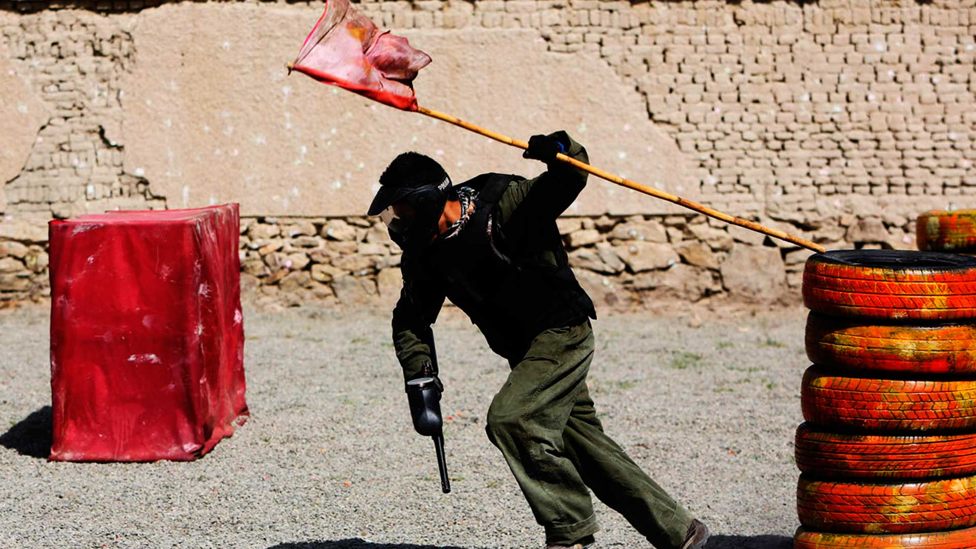 Jogador de paintball correndo com a arma de paintball em uma mão e na outra a bandeira que capturou.