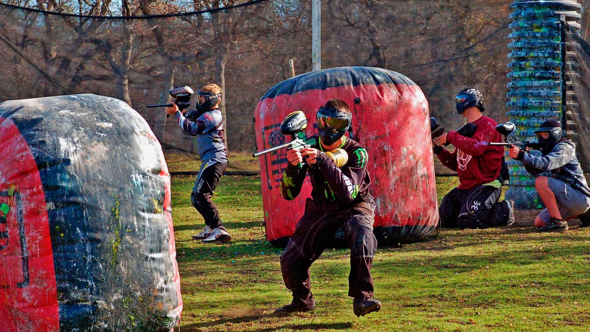 Campeonato de paintball. Na imagem aparece 4 pessoas do mesmo time, duas mais atrás, em posição defensiva, e duas pessoas avançando.