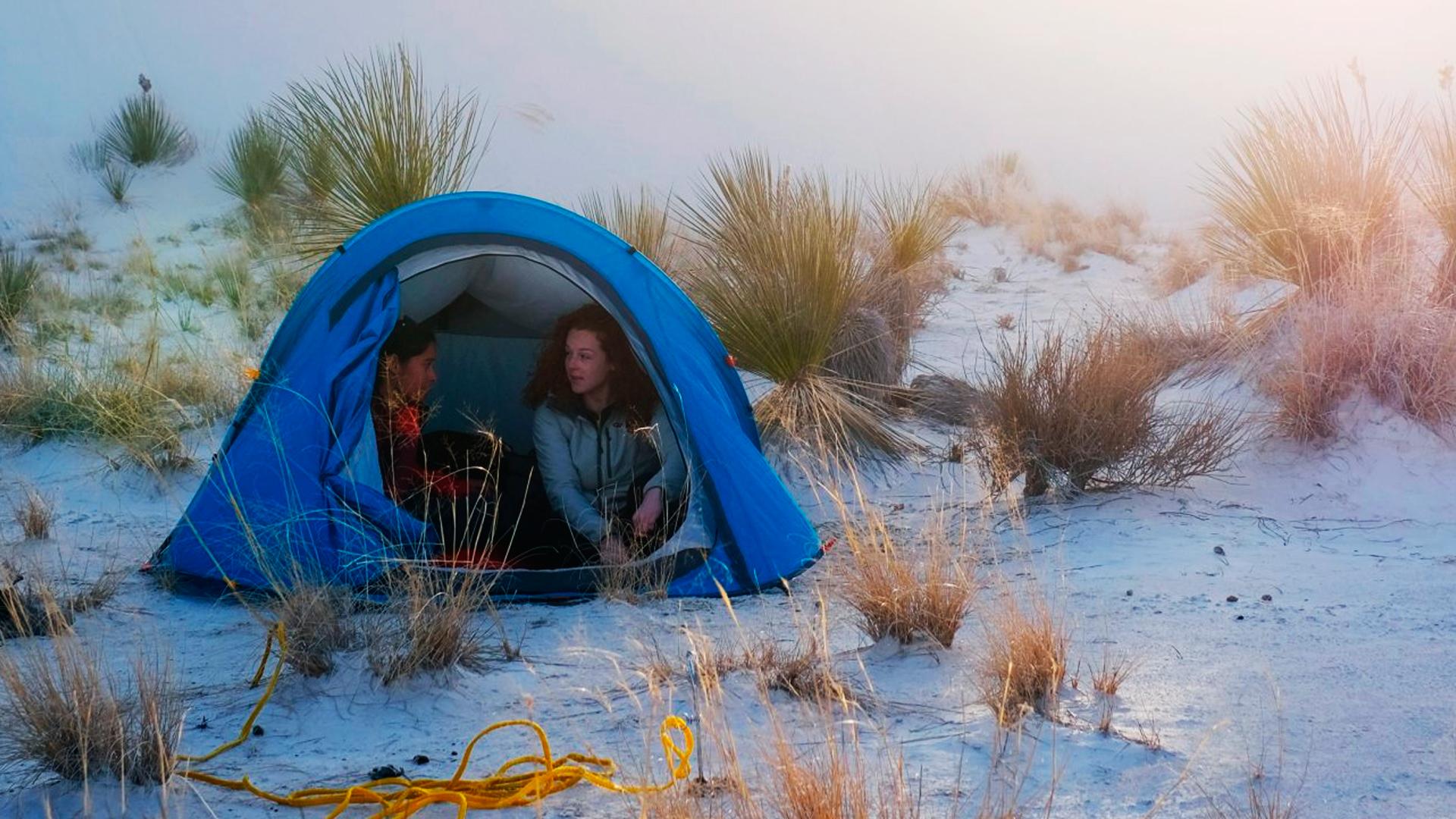Duas amigas dentro de uma barraca, que está em um local com bastante areia.