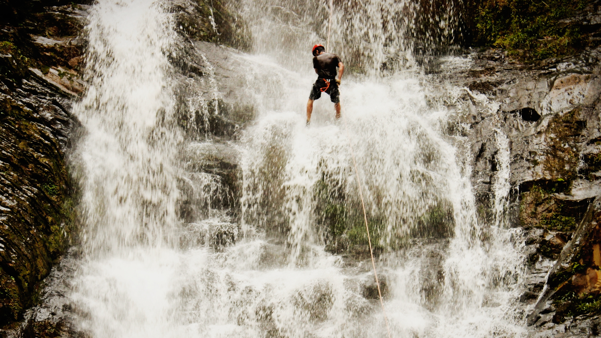 Homem praticando rapel em uma cachoeira.