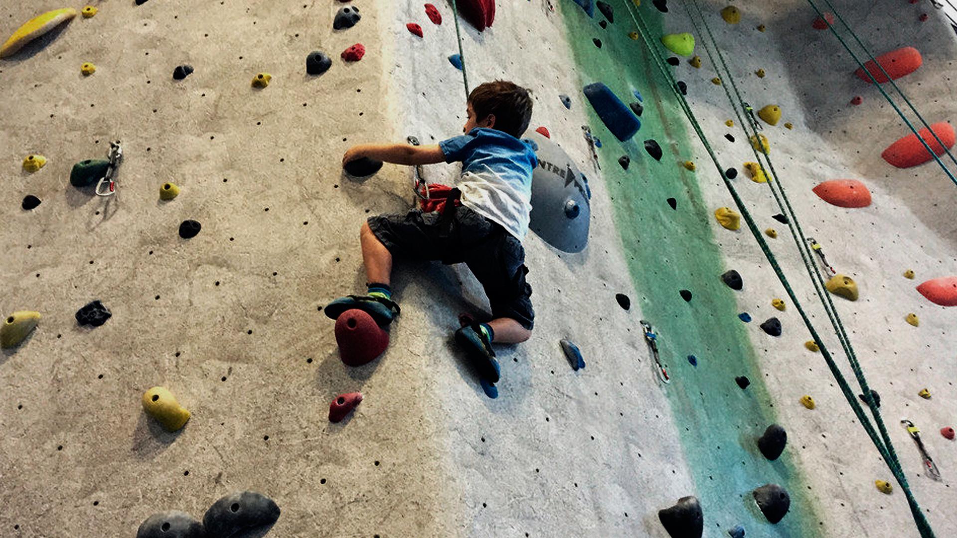 Criança praticando escalada indoor. Ela está se segurando nas agarras e com a corda de segurança amarrada em seu corpo.