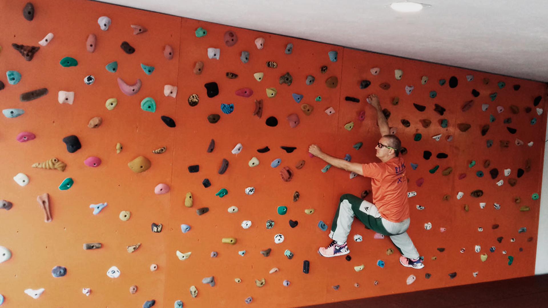 Homem praticando escalada indoor em uma parede laranja.