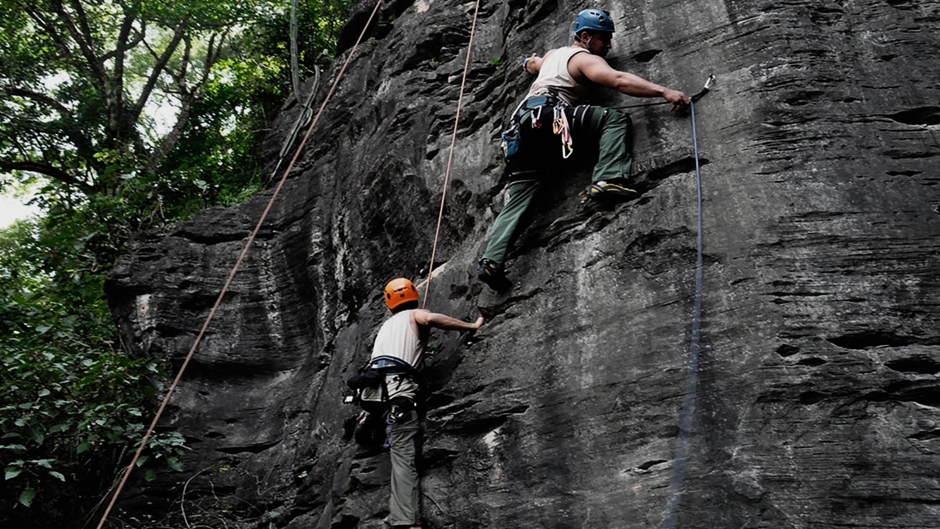 Duas pessoas praticando escalada outdoor. Ambas com capacete de segurança e também cordas de segurança.