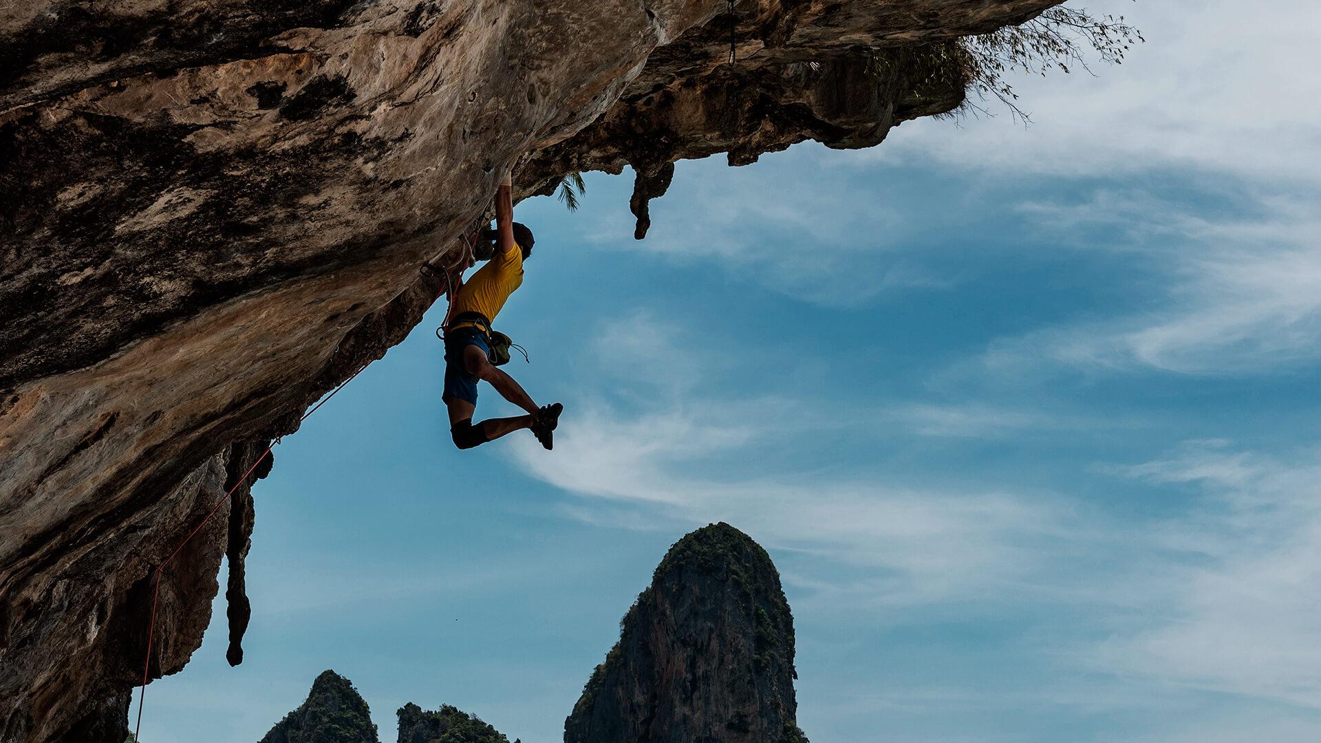 Homem praticando escalada em uma montanha. Está pendurado na montanha, no fundo um céu bem azul.