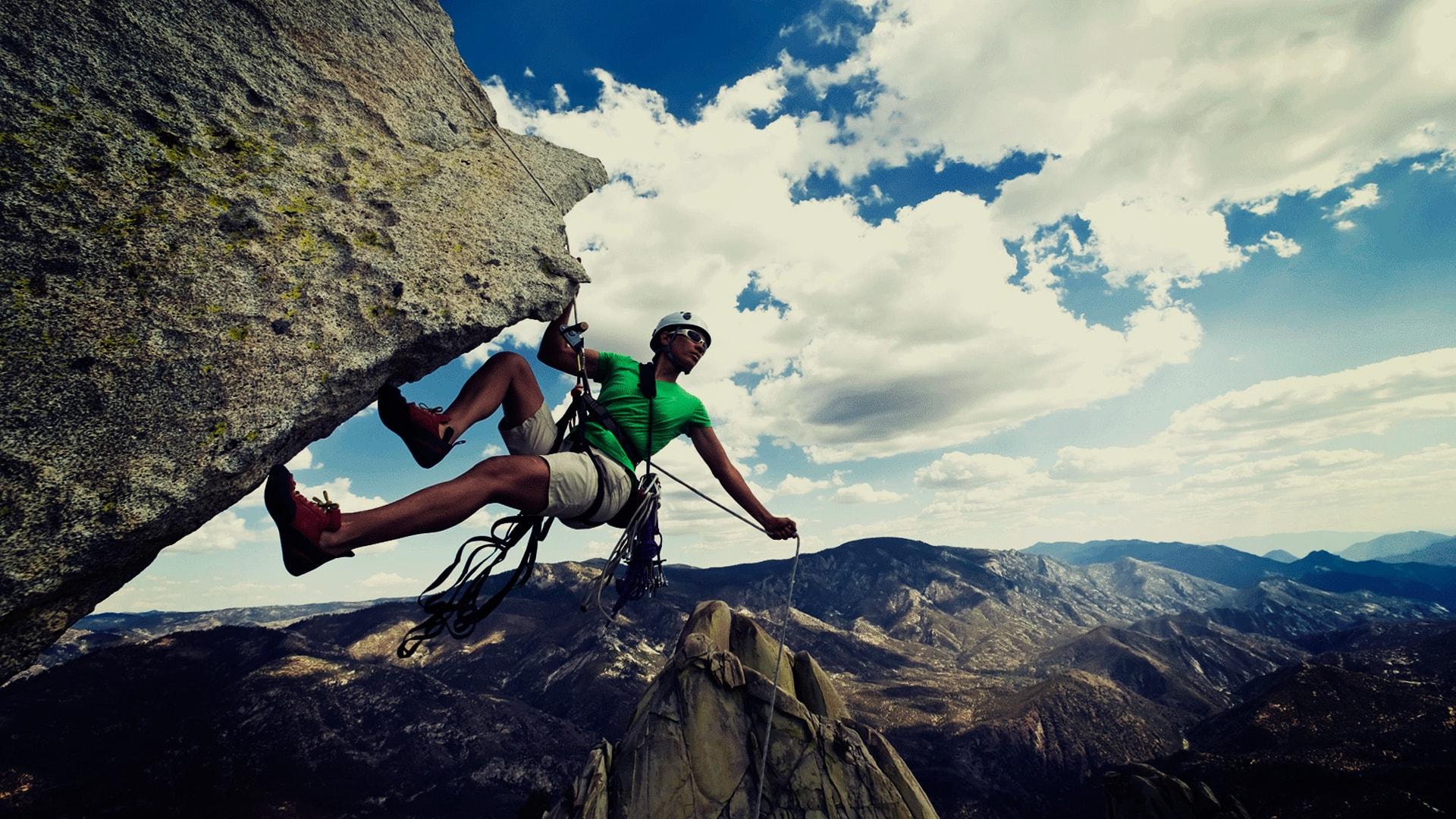 Homem praticando alpinismo em uma montanha muito alta. Ao fundo tem várias montanhas e um céu bem azul, com nuvens.