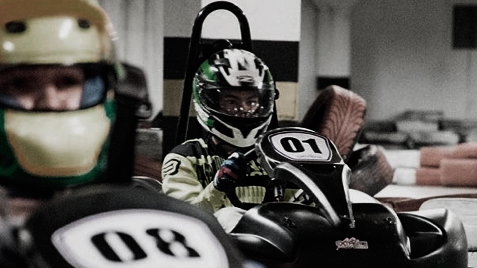 Dois pilotos de kart, preparados para iniciar a corrida no Kart Extra Curitiba, a maior pista de kart indoor de Curitiba