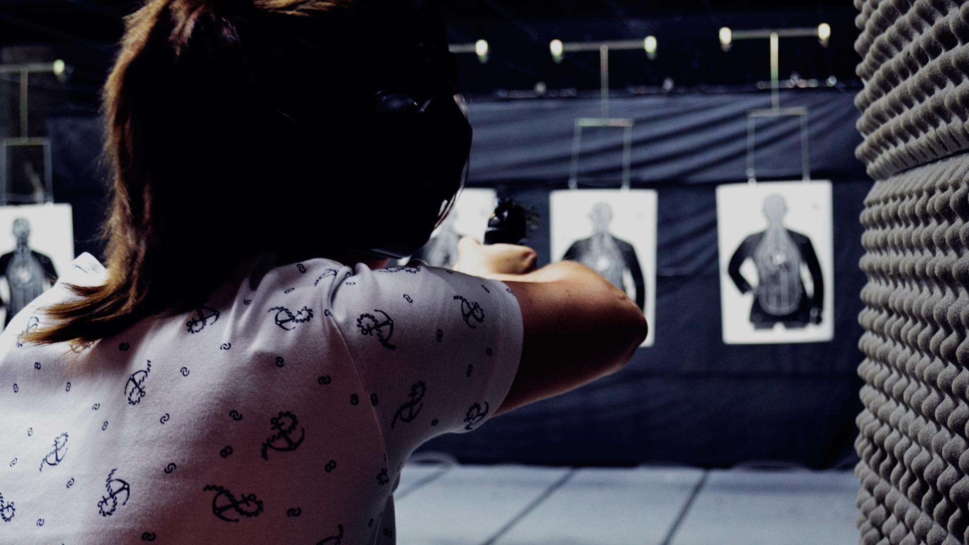 Mulher mirando em um alvo dentro de um estande de tiro. Ela esta de costas, com protetor auricular e óculos de proteção. Está mirando com uma pistola, que está apontada para o alvo do estande.