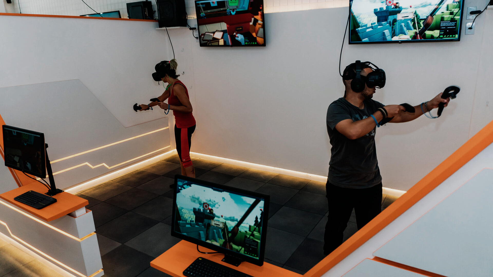 A imagem é atual e mostra um casal utilizando a realidade virtual para jogar. O ambiente é uma sala com várias telas, parecendo bastante uma exposição.