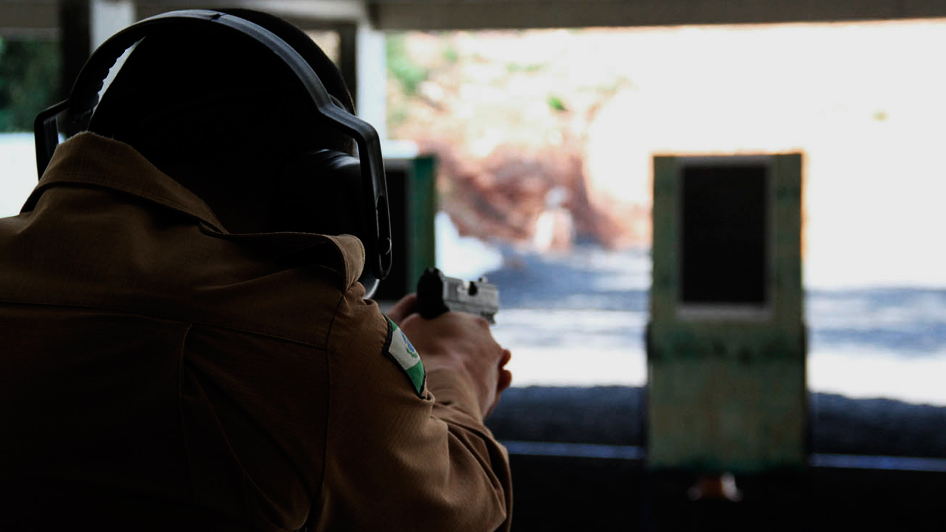 Homem praticando o tiro esportivo. Ele está de costas, utilizando uma farda de policial, um protetor auricular e com a arma apontada para o alvo, que se encontra no fundo da imagem.