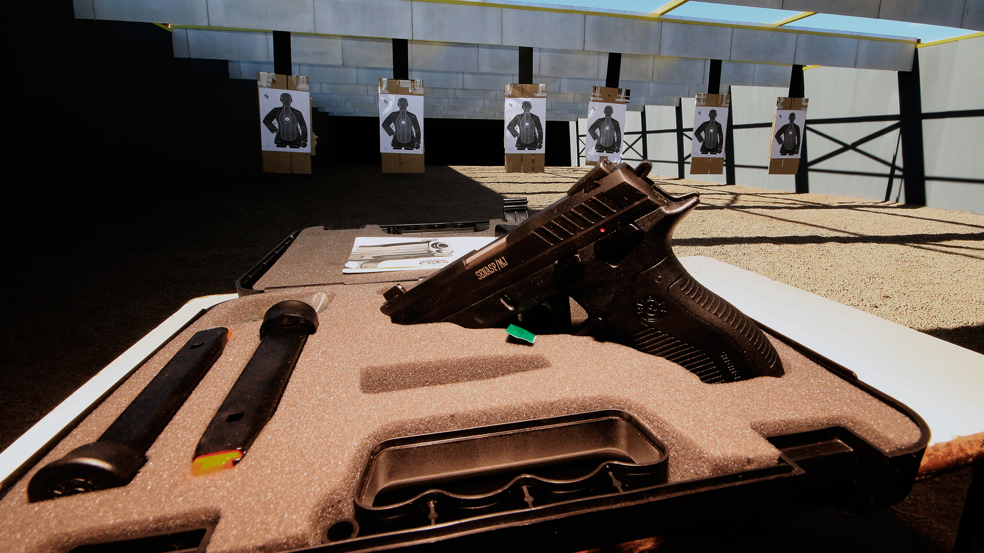 Local de estande de tiro. Na imagem tem uma caixa de uma pistola, com a arma posicionada para a fotografia. Ao fundo tem 6 alvos.