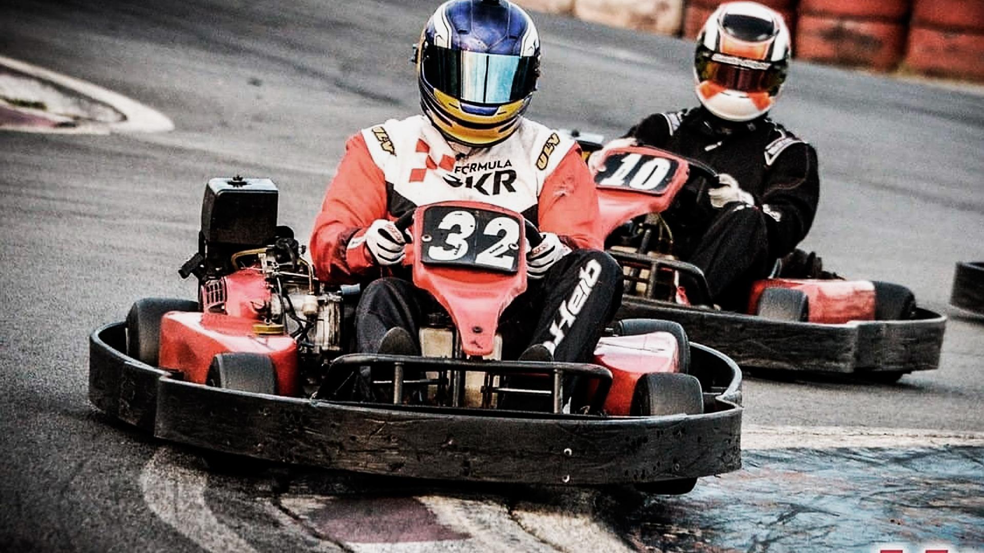 Dois pilotos fazendo uma curva na pista de kartódromo. O piloto da frente está passando em cima da zebra na curva.