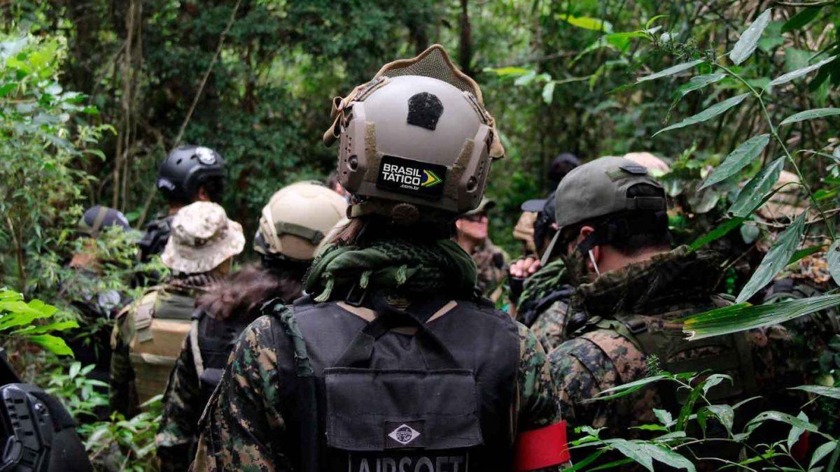 Na imagem há um time de airsoft, devidamente equipado, explorando um campo de airsoft ao ar livre.