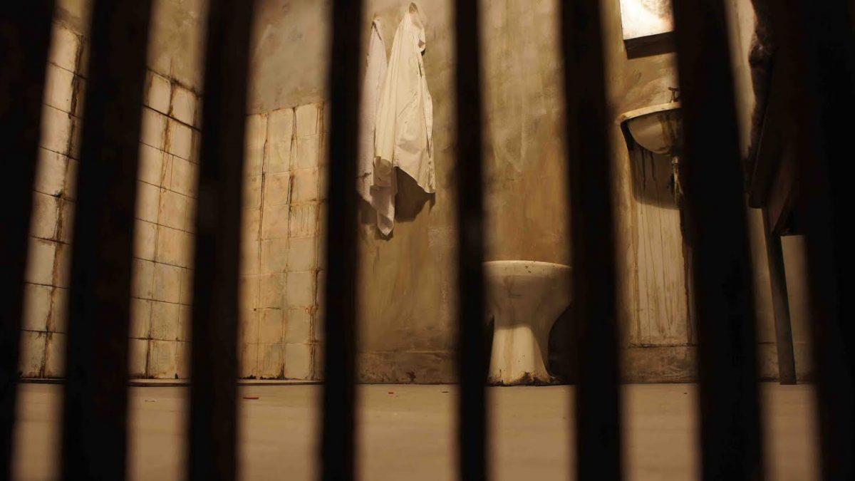 Na imagem aparecem grades e ao fundo tem uma pequena prisão, com uma pia, um vaso sanitário e uma toalha no varal.