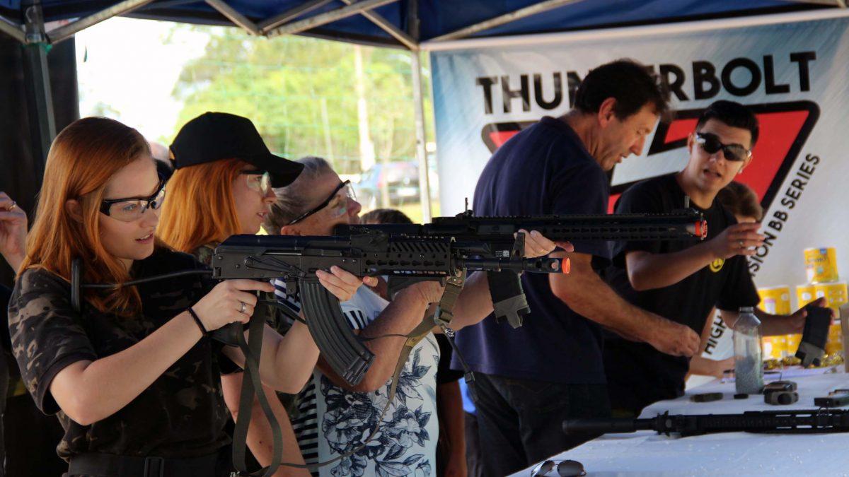 Na imagem há um estande de tiro, com três mulheres segurando armas de airsoft, prontas para atirar.