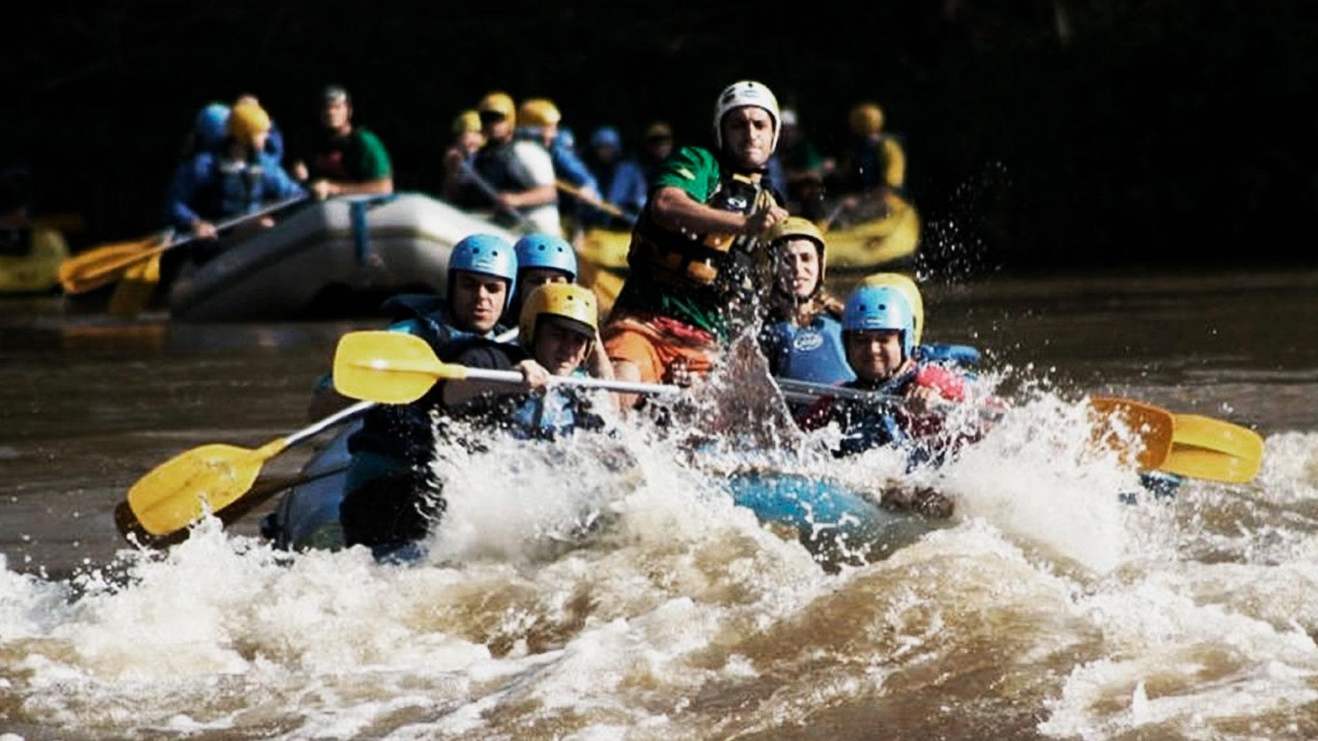 Grupo de pessoas em um bote azul praticando rafting no rio ribeira, em Cerro Azul.