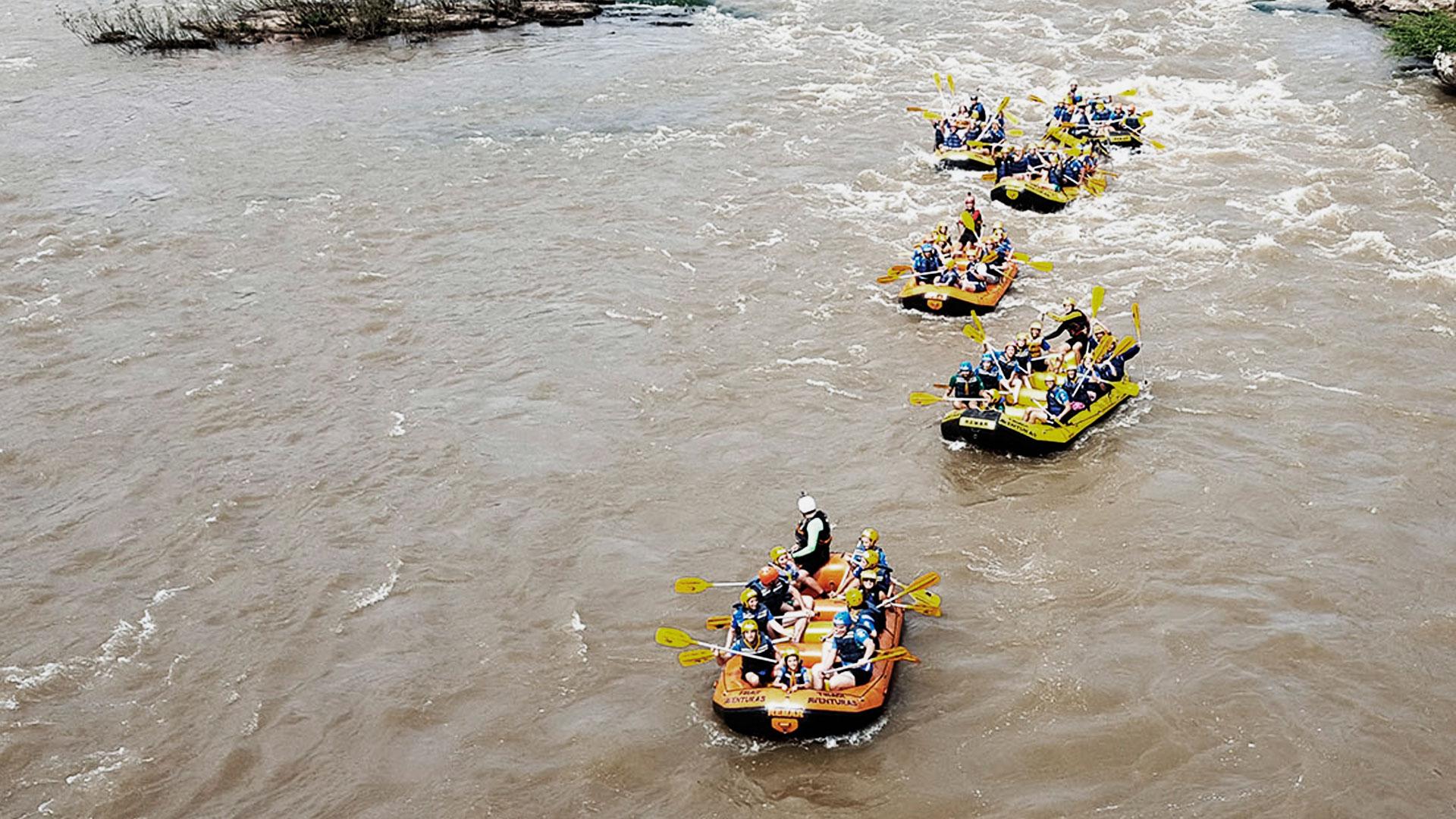 Grupo de pessoas em 6 botes praticando rafting no rio tibagi, em Tibagi.