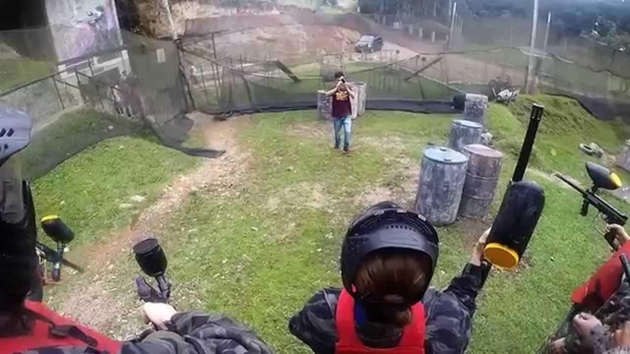 Na imagem tem 3 pessoas de costas, segurando o marcador de paintball. Logo em frente tem um menino tirando foto. Eles estão no campo São José Eco Paintball.
