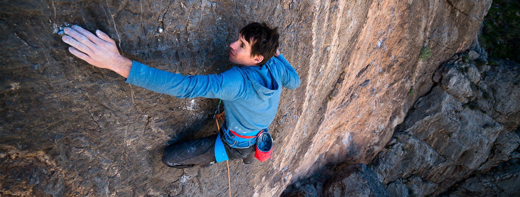 Na imagem, o alpinista Alex Honnold está escalando um paredão, ele usa um casaco azul e está utilizando corda, já que é uma escalada teste.