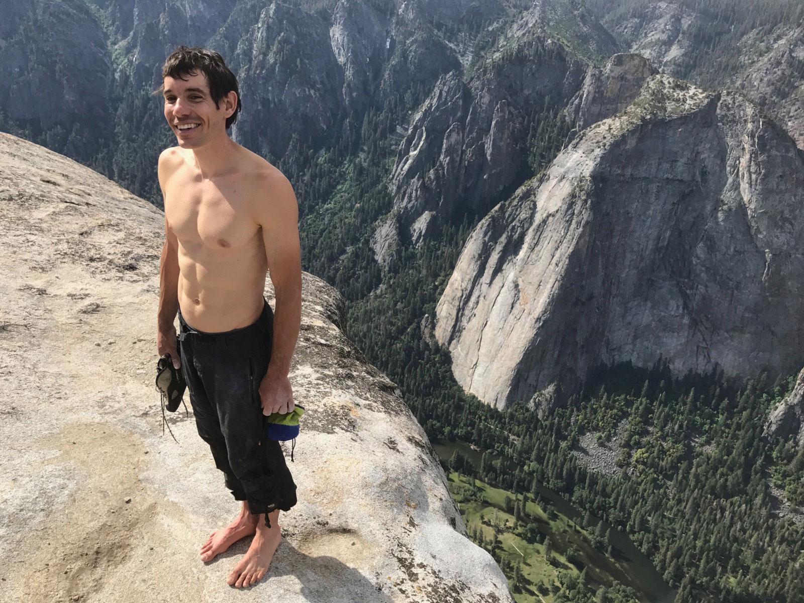 Na imagem, Alex Honnold está descalço, segurando seu tênis de escalada. Ele está no topo de um paredão, e sorri para a câmera.