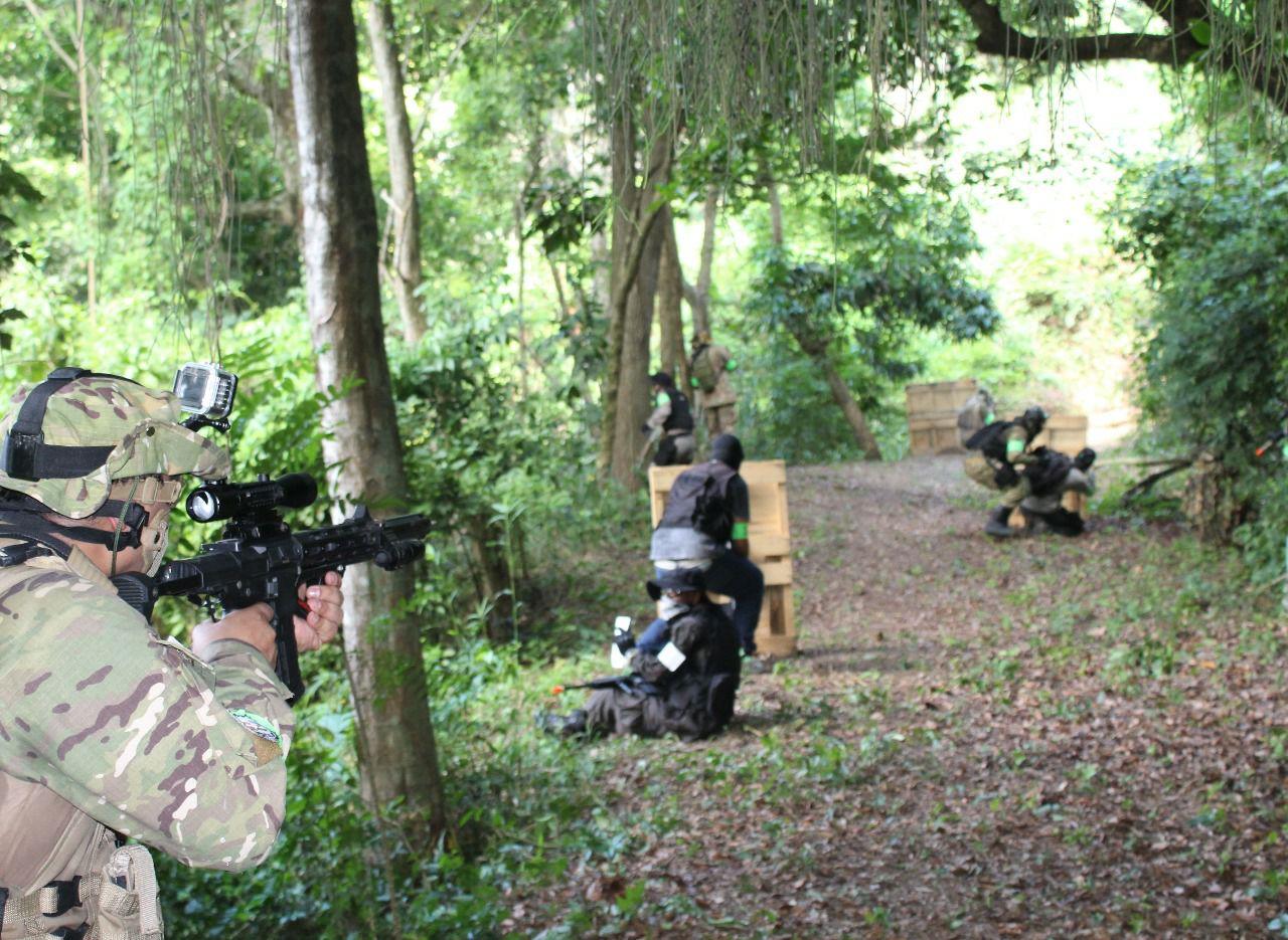 Na imagem, três jogadores de airsoft se posicionam atrás dos obstáculos e apontam suas armas.