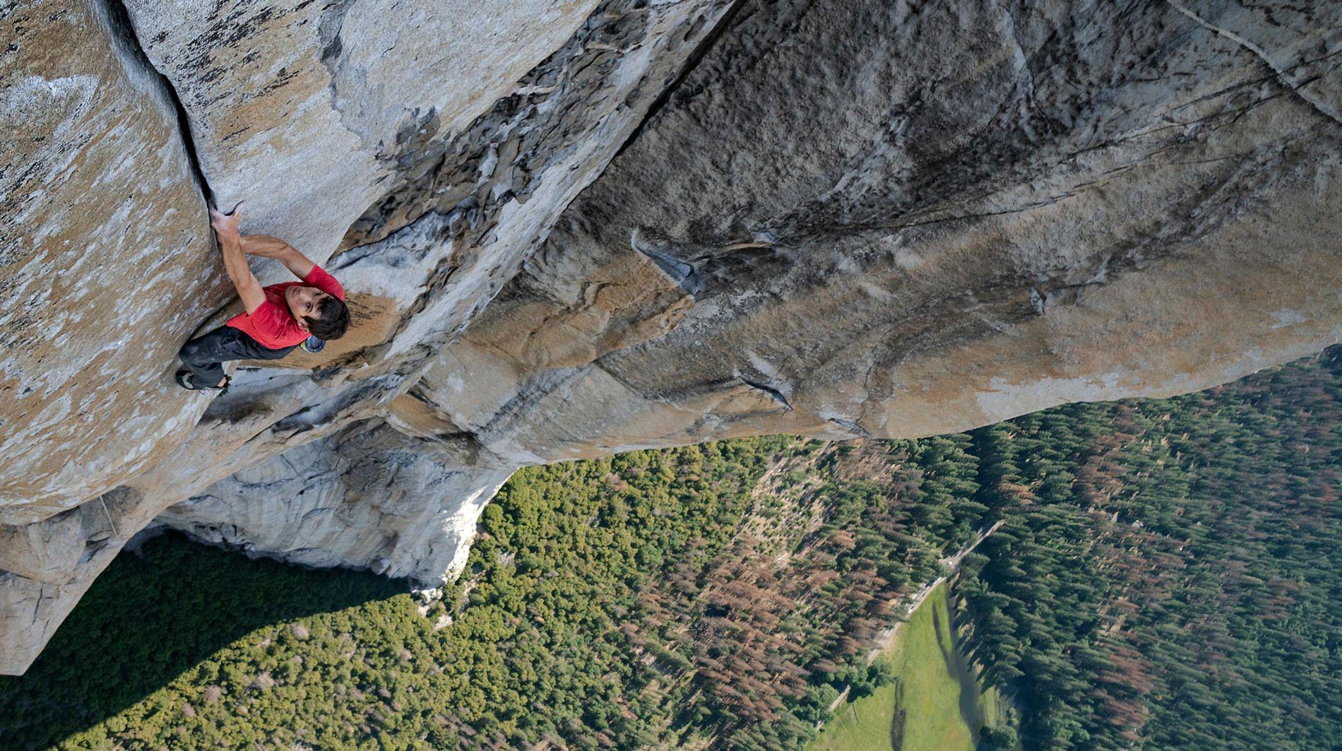 Na imagem, Alex Honnold escala um paredão gigante. Ele está com as mãos entre um pequeno vão, sem protecão alguma.