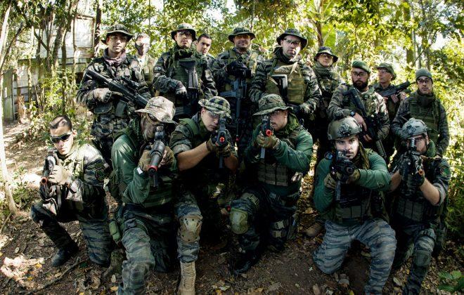 Na imagem, temos um time de airsoft composto por homens, todos trajados com roupas para a prática. Ao fundo, um campo no estilo Selva.