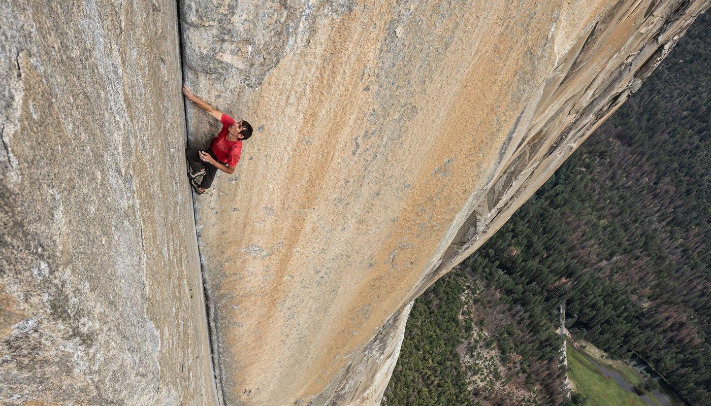 Na imagem, Alex aparece escalando um paredão enorme. O alpinista está com as mãos entre uma abertura da rocha.
