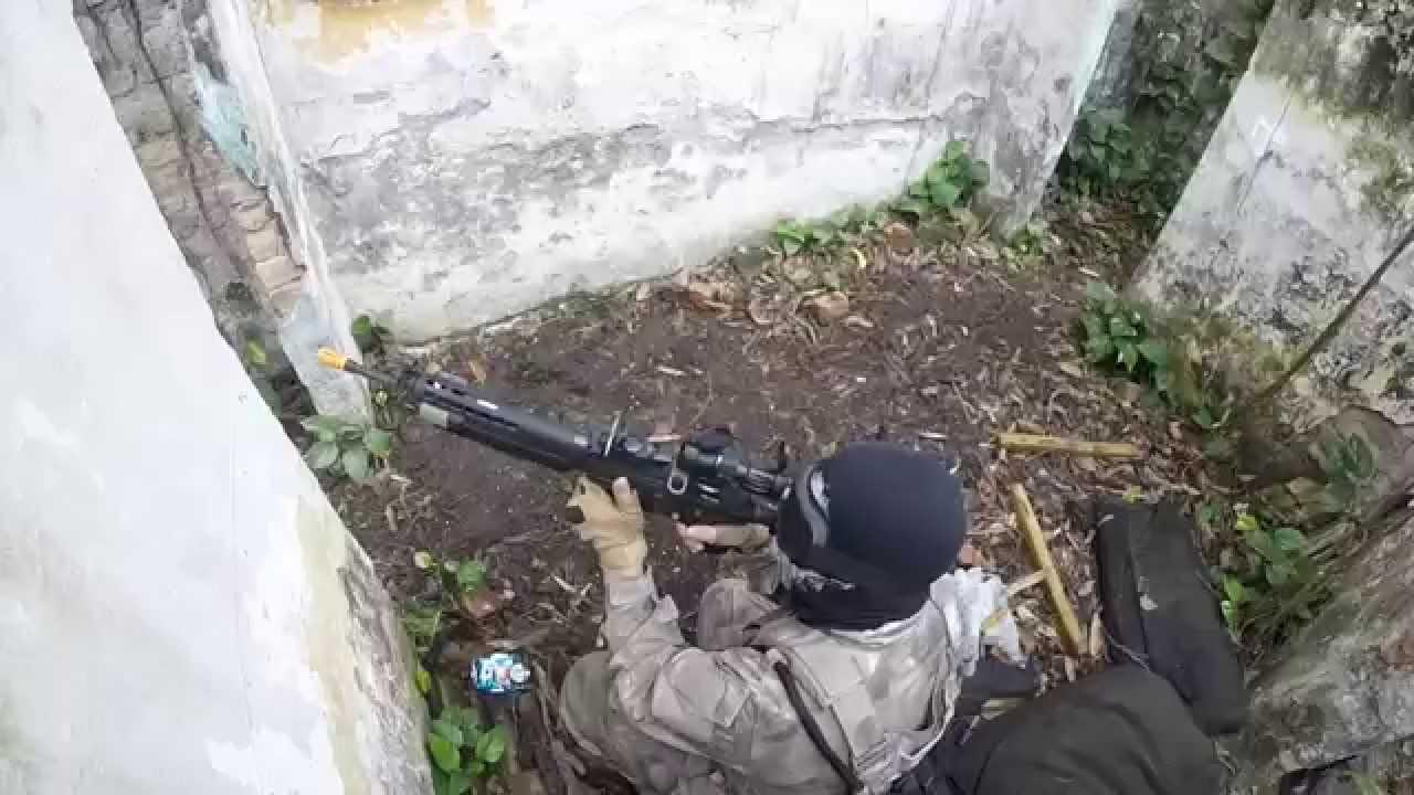 Na imagem, um homem com as vestimentas próprios para o airsoft, segura uma arma e aponta para fora do seu esconderijo.