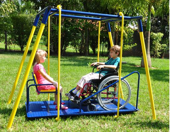 Imagem de um brinquedo adaptado onde um cadeirante brinca de balanço.