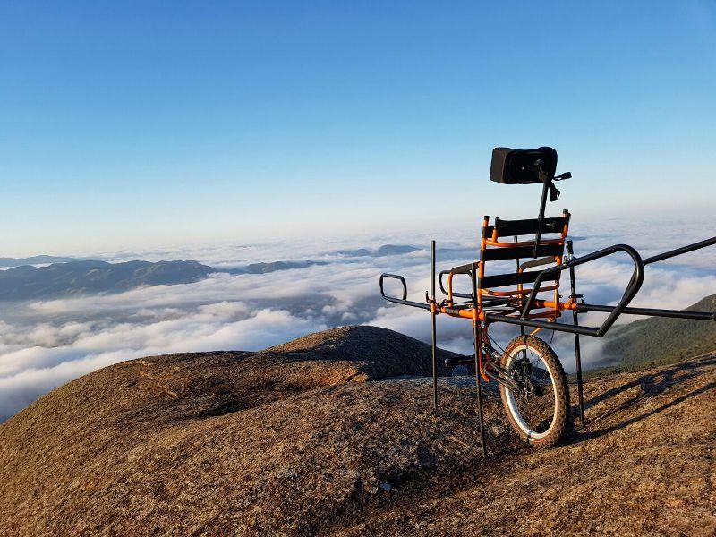 Na imagem, a cadeira adaptada está no topo de uma montanha. Ela só tem uma roda.