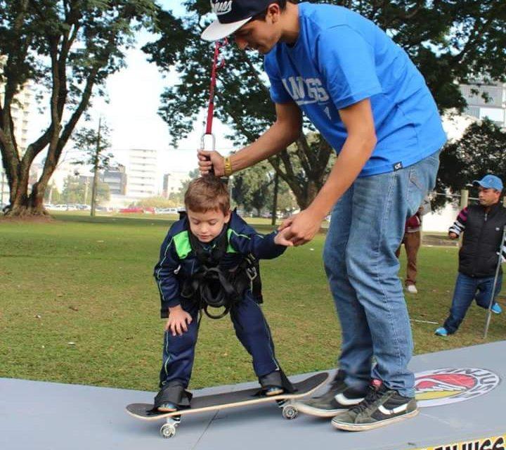 Na imagem, um garoto que está sendo segurado pelo instrutor e por cordas, anda de skate adaptado.