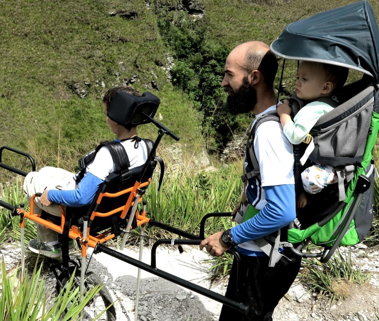 Na imagem, Juliana usa a cadeira adaptada com a ajuda de Guilherme, que carrega o filho Benjamin com a ajuda de um suporte nas costas.