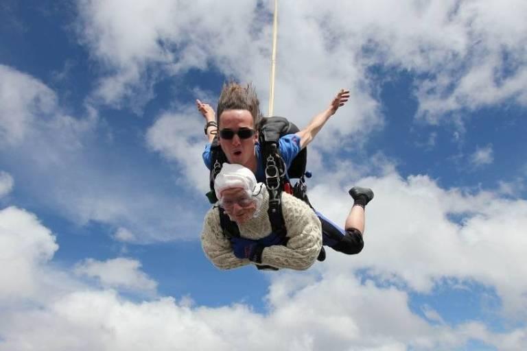 Na imagem, uma senhora de 102 anos está no meio do seu salto de paraquedas, com o instrutor atrás dela.