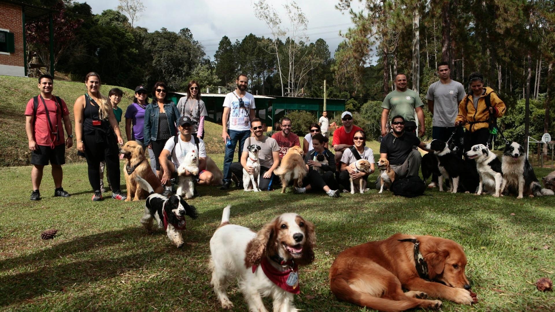 Na imagem, cachorros e seus donos posam para a foto, em um ambiente natural.