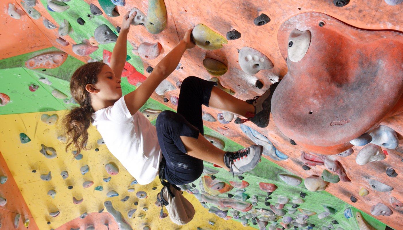 Na imagem, uma criança escala um paredão de escalada indoor.