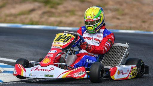 Na imagem, um piloto de kart está em movimento dentro do seu carro de kart.