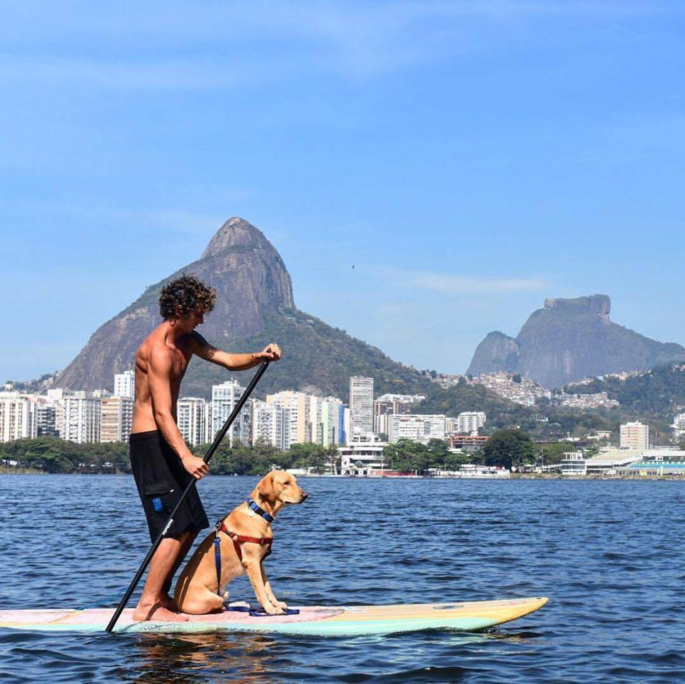 Na imagem, um cão e seu dono estão em cima de uma prancha de stand up paddle.