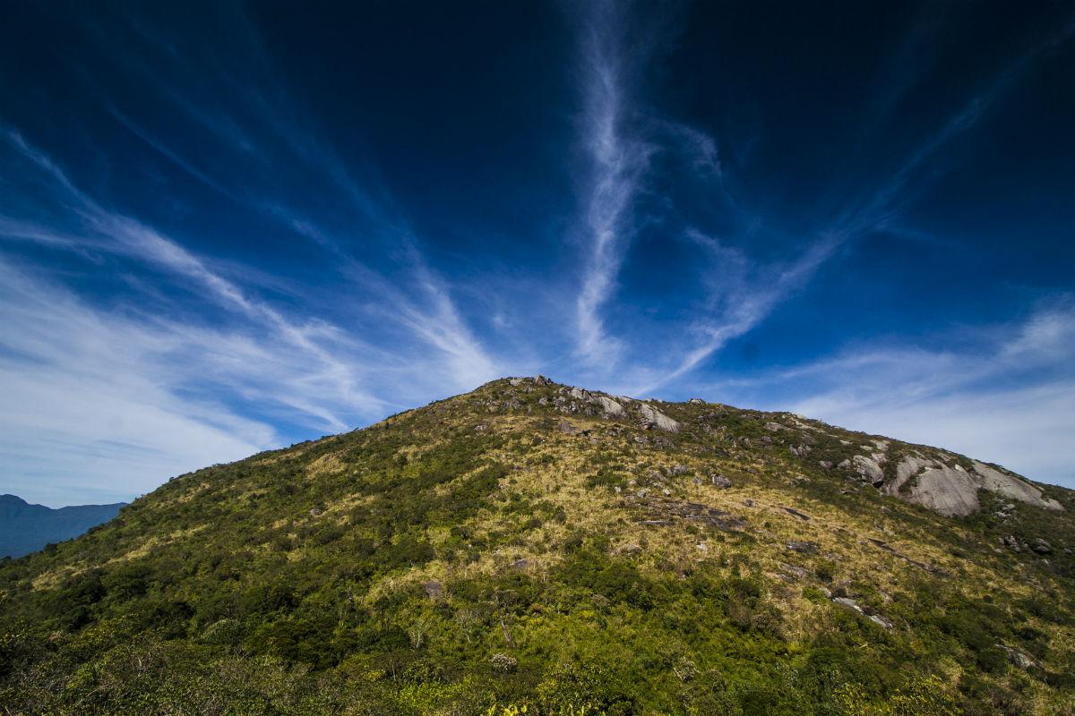 Na imagem, temos o pico do Morro do Anhangava. Ao fundo, uma paisagem de céu muito azul e iluminado.