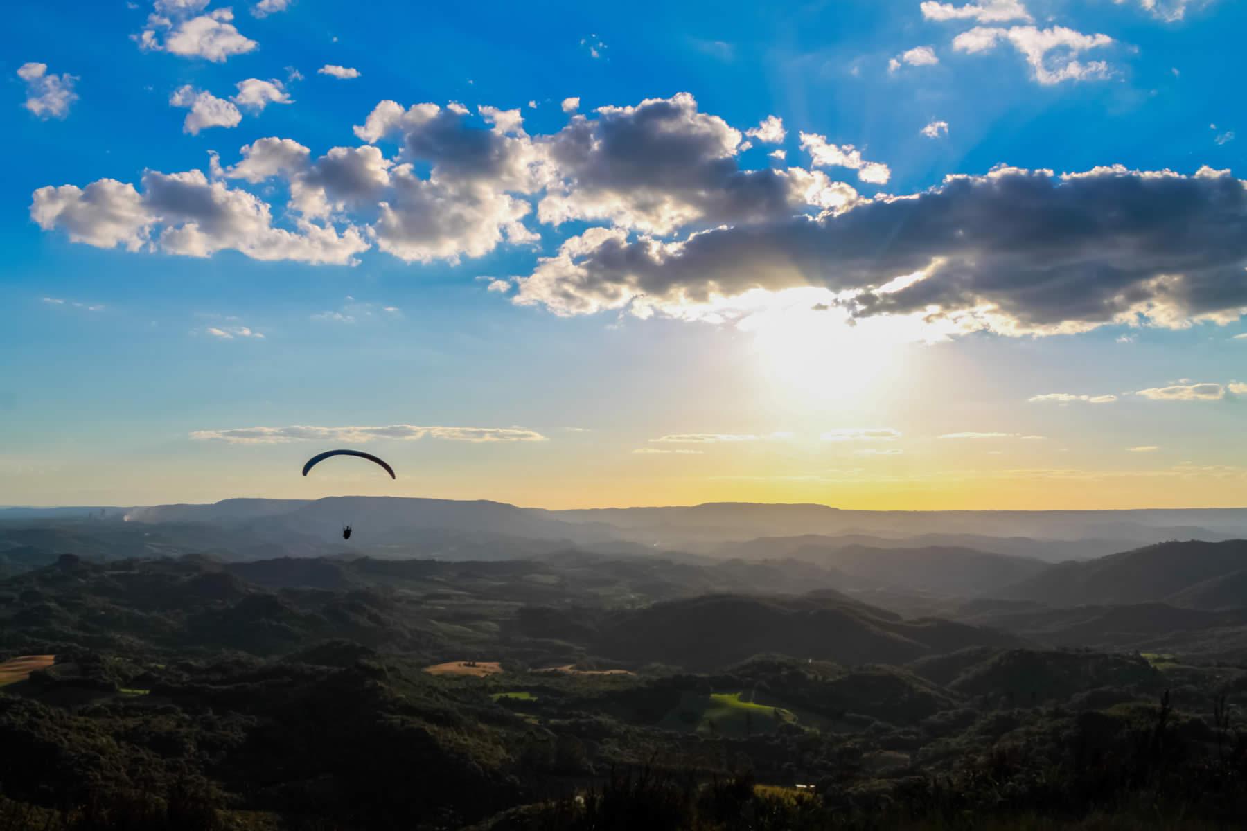 Na imagem, temos a vista do Morro do Cal. O céu está muito azul e tem alguém de parapente voando sob os morros menores.