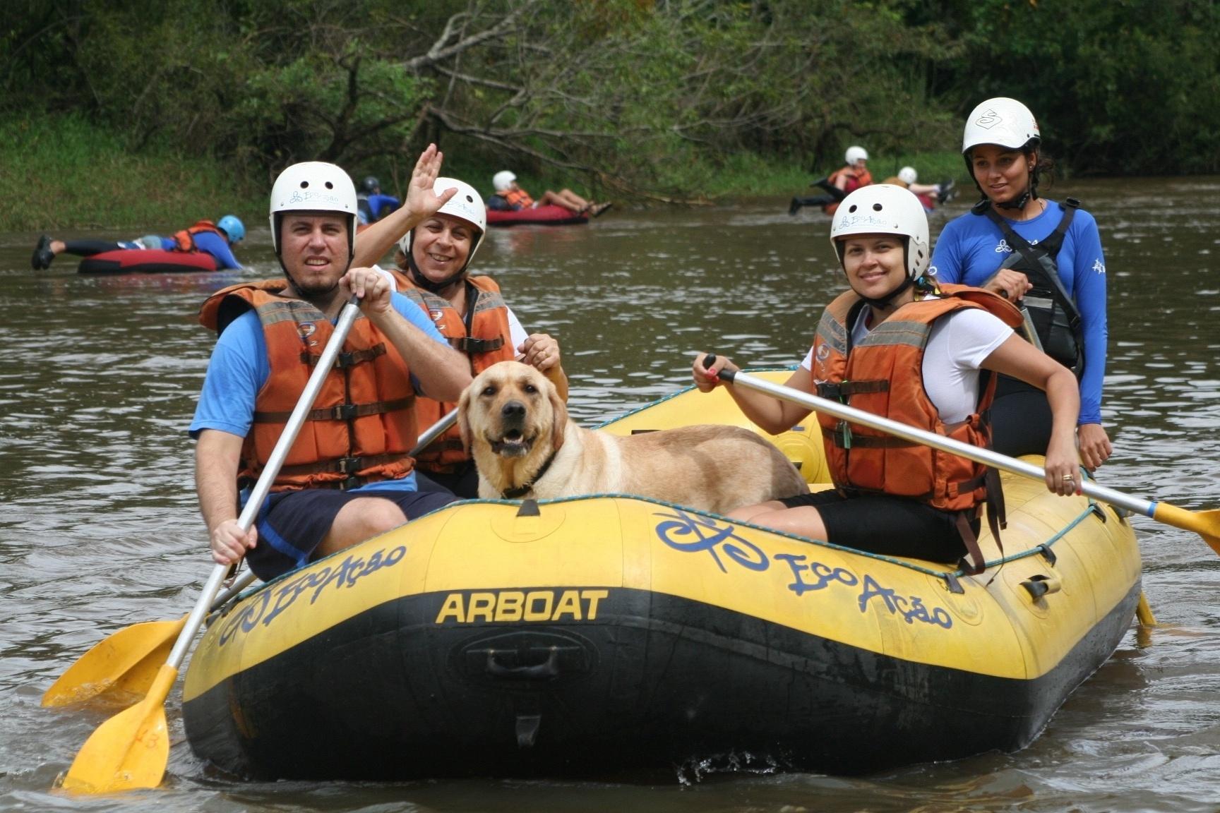Na imagem, um grupo de 4 pessoas e 1 cachorro, estão sobre um bote em uma corredeira de água.