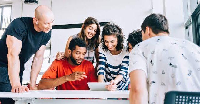 Na imagem, pessoas jovens, dois homens e duas mulheres se reunem em uma mesa de trabalho.