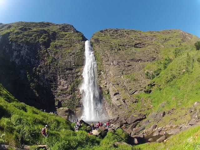 Na imagem, há uma cachoeira em meio dois montes. Ela forma uma piscina natural onde as pessoas se banham.
